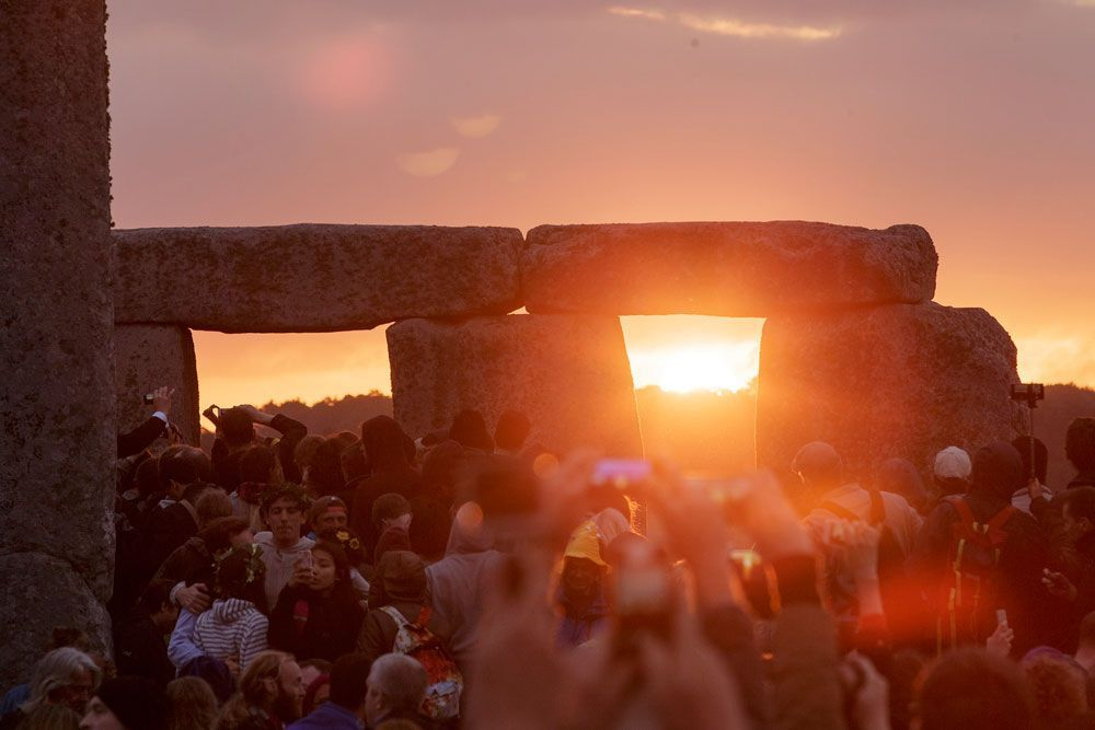 The sun in it's entirety shines through a gateway of Stonehenge