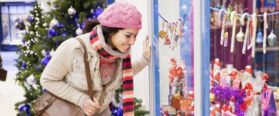 Woman looking in shop window at chocolate display.