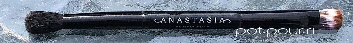 THE ANASTASIA RIVIERA EYE SHADOW PALETTE DOUBLE-ENDED BRUSH, A FLAT SIDE ON ONE END, AND A FLUFFY BRUSH ON THE OTHER END
