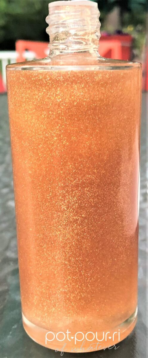 BECCA CHRISSY TEIGEN GLOW BODY OIL FORMULA SEEN THROUGH BOTTLE