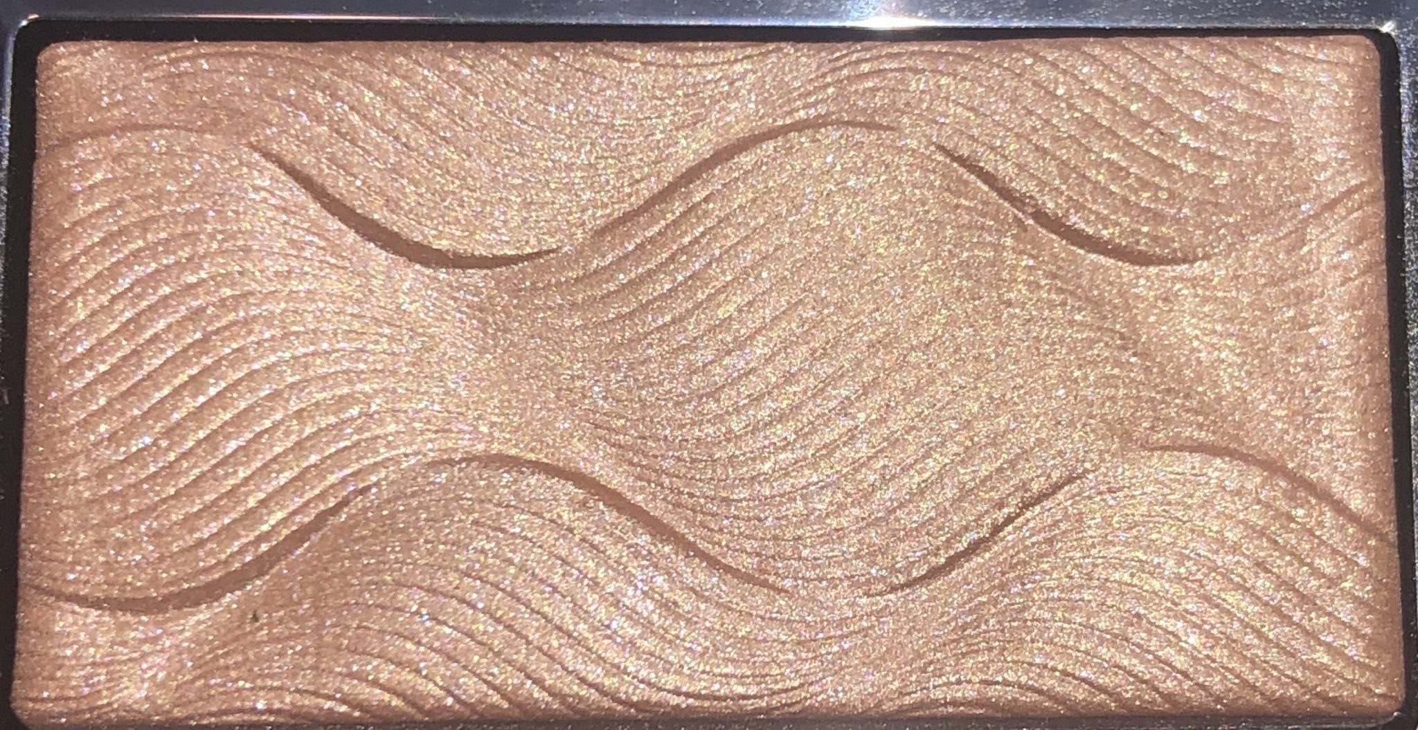 THE CORAL PALETTE'S HIGHLIGHTER IS A CHAMPAGNE SHADE WITH A SUBTLE SHIMMER