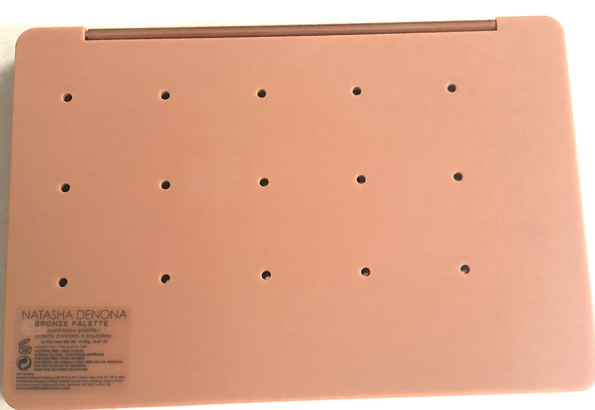 THE BACK OF THE BRONZE EYESHADOW PALETTE HAS PIN HOLES SO YOU CAN REMOVE THE EYESHADOW PANS