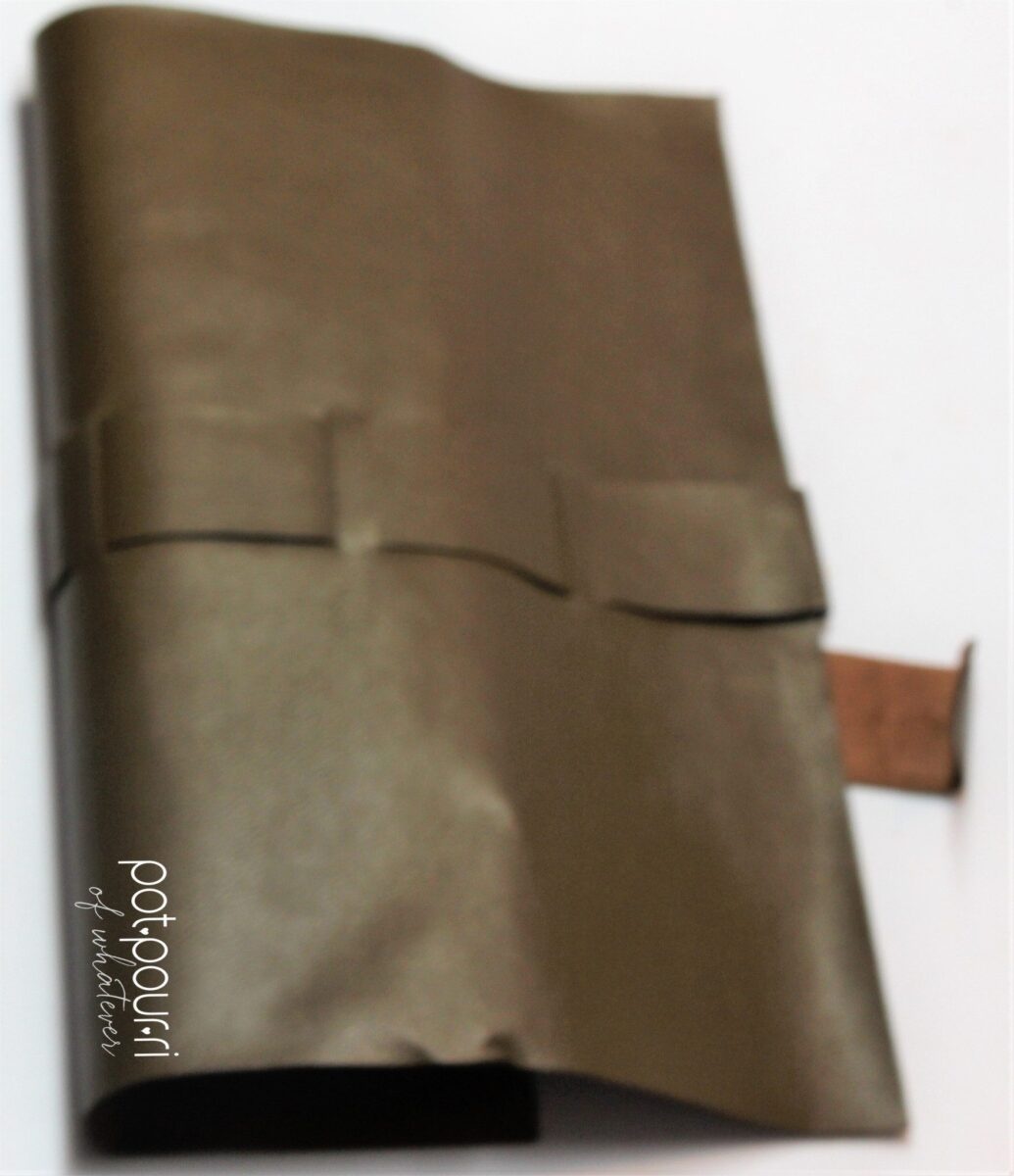 the brush roll is brown leatherette, lightweight with the logo in gold