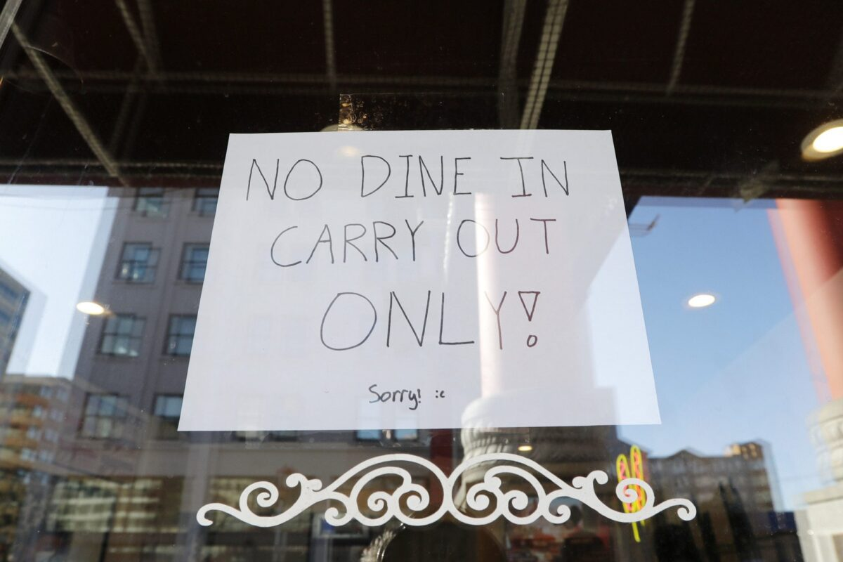A sign posted in a restaurant window in the Chinatown-International District advises of only take out orders Monday, March 16, 2020, in Seattle. Washington Gov. Jay Inslee on Monday ordered all bars, restaurants, entertainment and recreation facilities to temporarily close to fight the spread of the new coronavirus in the state with by far the most deaths in the U.S. from the COVID-19 disease. Take out and delivery food orders are still allowed. (AP Photo/Elaine Thompson)
