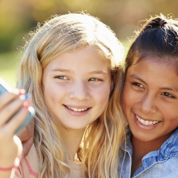 Two Girls Taking Selfie With Mobile Phone Smiling To Camera