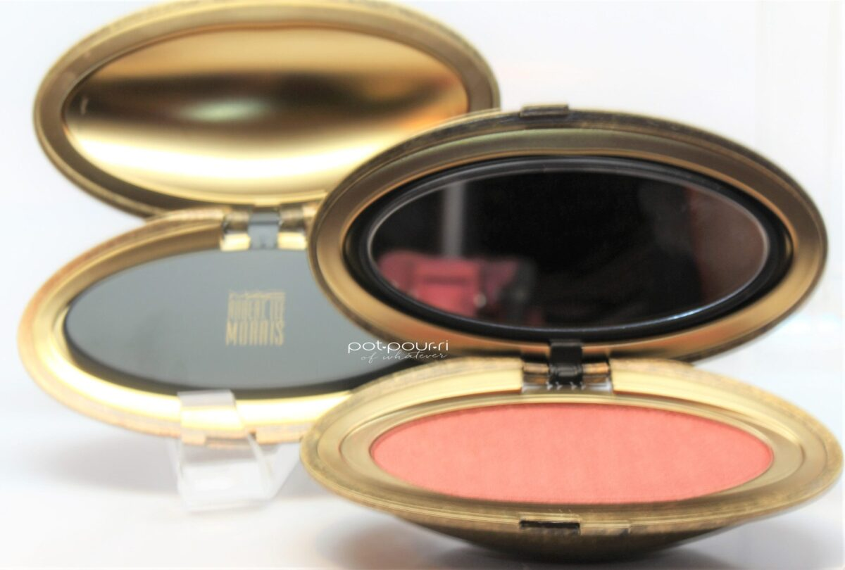 inside the face powder compact, under the matte black insignia is a mirror