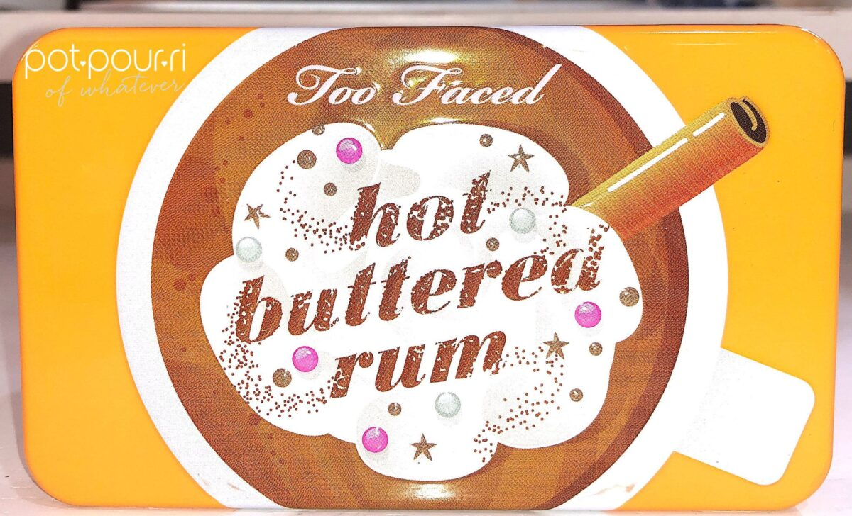 THE HOT BUTTERED RUM MINI PALETTE COMPACT WITH RAISED DESIGN ON THE FRONT OF THE METAL CASE
